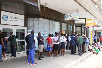 Zimbabweans wait to withdraw money.Photographer: Tafadzwa Ufumeli/Anadolu Agency/Getty Images